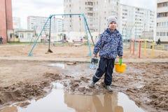 使用在一个泥泞的水坑的男孩 免版税库存照片