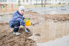 使用在一个泥泞的水坑的男孩 免版税图库摄影
