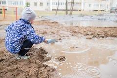 使用在一个泥泞的水坑的男孩 库存图片