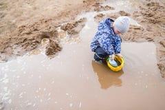 使用在一个泥泞的水坑的男孩 图库摄影
