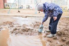 使用在一个泥泞的水坑的男孩 免版税库存图片
