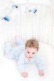 使用在一个白色圆的小儿床的逗人喜爱的婴孩 免版税库存照片