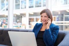 使用在一个长沙发的微笑的女实业家电话有膝上型计算机的 免版税库存照片