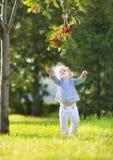 使用在一个晴朗的秋天公园的美丽的白肤金发的卷曲女婴 免版税库存照片