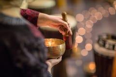 使用在一个tibetian唱歌碗的妇女 库存图片