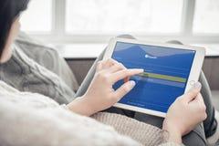 使用在一全新的苹果计算机iPad的妇女Expedia app赞成 库存图片