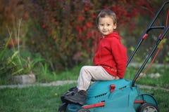 使用在一台割草机的小男孩在秋天 免版税图库摄影