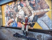 使用在一台经典土耳其民间音乐仪器的街道音乐家 免版税库存照片