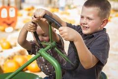 使用在一台老拖拉机的可爱的年轻男孩外面 免版税图库摄影