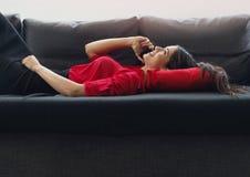 使用在一名sofaBeautiful年轻女实业家的美丽,年轻女实业家一个电话谈话在沙发的电话 库存图片