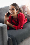 使用在一名sofaBeautiful年轻女实业家的美丽,年轻女实业家一个电话谈话在沙发的电话 免版税库存图片