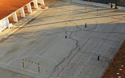 使用在一所公开小学的操场的孩子在日落 库存照片