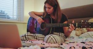 使用在一把吉他的特写镜头吸引人少年女孩在她的屋子里在学校享受时间一会儿的作为断裂以后 股票视频