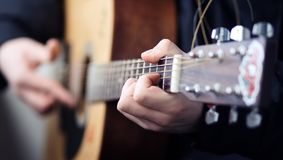使用在一把美丽的木声学吉他的一个人 免版税库存照片