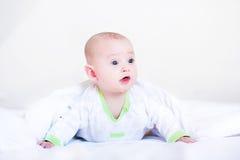 使用在一条白色毯子下的滑稽的男婴 免版税库存照片