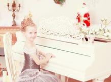 使用在一架白色大平台钢琴的小女孩 免版税库存照片