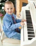 使用在一架白色大平台钢琴的小男孩 免版税图库摄影