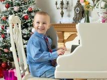 使用在一架白色大平台钢琴的小男孩 免版税库存图片