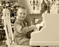 使用在一架白色大平台钢琴的小男孩 免版税库存照片