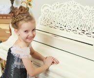 使用在一架白色大平台钢琴的小女孩 库存照片