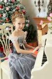 使用在一架白色大平台钢琴的小女孩 库存图片