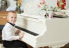 使用在一架白色大平台钢琴的小男孩 库存照片
