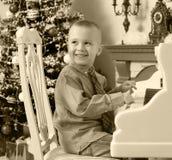 使用在一架白色大平台钢琴的小男孩 图库摄影