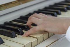 使用在一架白色钢琴的一个女孩的手,特写镜头 免版税图库摄影