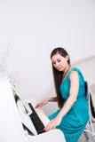 使用在一架白色钢琴的美丽的女孩 免版税图库摄影