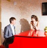 使用在一架红色钢琴的迷人的婚礼夫妇  免版税图库摄影