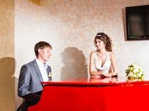 使用在一架红色钢琴的迷人的婚礼夫妇  免版税库存图片