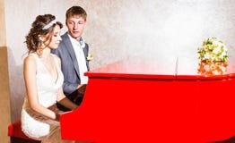 使用在一架红色钢琴的迷人的婚礼夫妇  库存图片