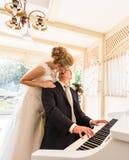 使用在一架钢琴的婚礼夫妇在屋子里 库存照片