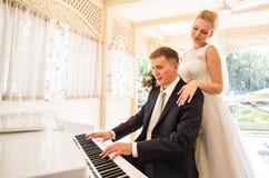 使用在一架钢琴的婚礼夫妇在屋子里 免版税图库摄影