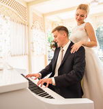 使用在一架钢琴的婚礼夫妇在屋子里 免版税库存照片