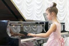 使用在一架黑大平台钢琴的一件美丽的桃红色礼服的女孩 使用在一架黑钢琴的女孩 图库摄影