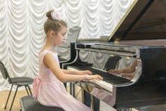使用在一架黑大平台钢琴的一件美丽的桃红色礼服的女孩 使用在一架黑钢琴的女孩 库存照片