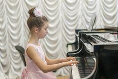 使用在一架黑大平台钢琴的一件美丽的桃红色礼服的女孩 免版税库存照片