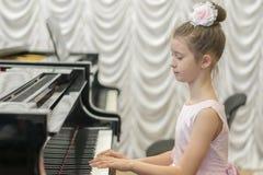 使用在一架黑大平台钢琴的一件美丽的桃红色礼服的女孩 免版税库存图片
