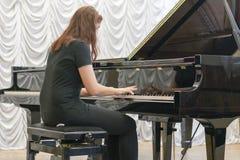 使用在一架黑钢琴的女孩 库存照片