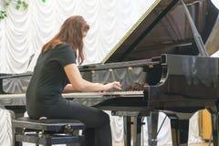 使用在一架黑钢琴的女孩 免版税图库摄影