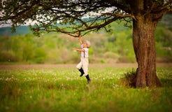 使用在一棵老树下的逗人喜爱的矮小的农夫男孩 库存图片