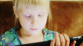 使用在一种数字式片剂的一个白肤金发的小女孩的画象 股票视频