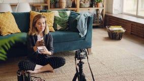 使用在三脚架的照相机美好的小姐vlogger记录关于新的构成产品和工具的录影 博客作者是 股票录像