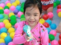 使用在与五颜六色的球的一个水池的亚裔女孩 免版税图库摄影