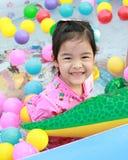 使用在与五颜六色的球的一个水池的亚裔女孩 库存照片