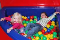 使用在与五颜六色的球的水池的女孩的男孩。 免版税库存照片
