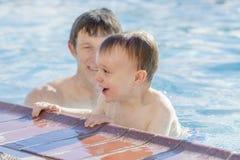 使用在与他的父亲的一个温暖的水池的小孩男孩在冬天期间 图库摄影