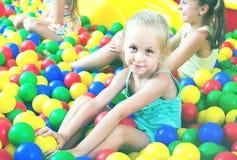 使用在与塑料多彩多姿的球的水池的女孩画象 免版税库存图片