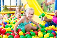 使用在与塑料多彩多姿的球的水池的女孩画象 库存图片